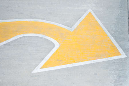 Yellow arrow traffic sign indicates minor road to turn left to major road. Compliance and warning concept
