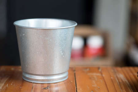 A metal buckets on wood table