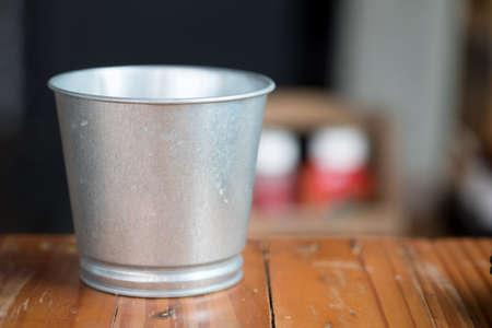 Ein Metalleimer auf Holztisch Standard-Bild