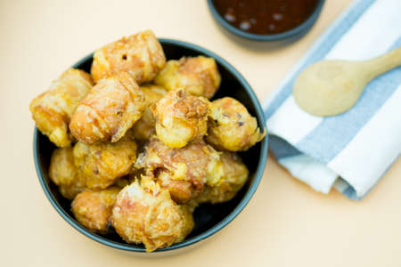 Fried meatballs is delicious in black bowl served with sweet sauce. Imagens
