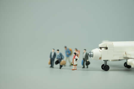 Miniature people : People of travellers with airplane on arrival