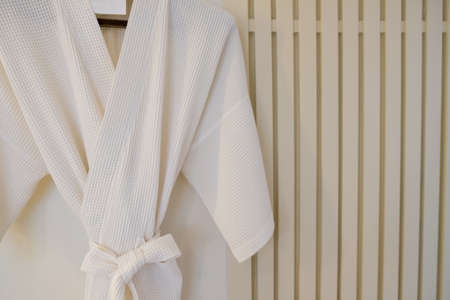 White bathrobe on a hanger on the wall in the bathroom.