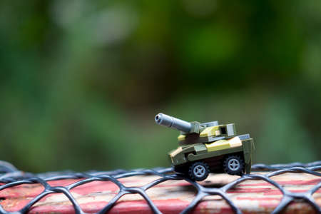 Miniature toys plastic tank on nature background. Concept of sample picture of war scenario