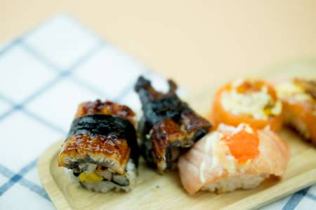 Salmon Sushi and Smoked Eel Sushi Roll on wood tray Stock Photo - 128806706