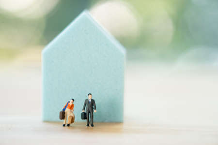 Miniature people : couple moving to new home. Concept of new life