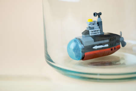Miniature plastic toy submarine in glass on yellow background