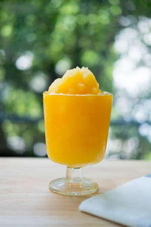 Glass of organic fresh orange smoothie juice.  Homemade juice with nature background