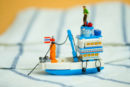 Miniature people stand on generic Thai fishing ship or tourist ship modified from fishing ship for go to destination. Travel in Thailand