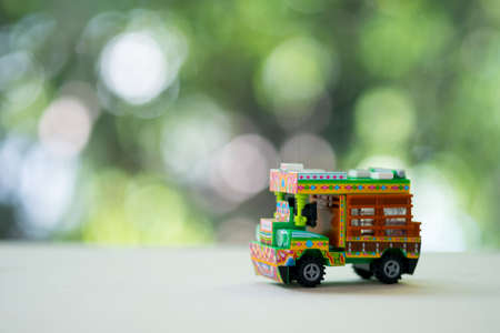 Miniature toy Thai farming trucks on wood table with nature background