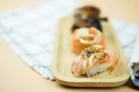 Various kinds of sushi served on wooden tray.  Sushi is a delicious Japanese dish Stock Photo