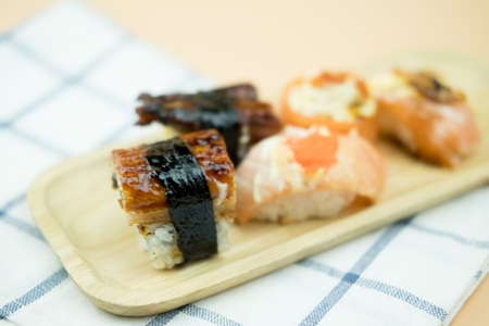 Various kinds of sushi served on wooden tray.  Sushi is a delicious Japanese dish Stock Photo - 129006264