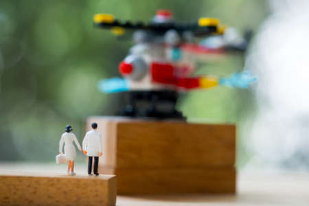 Rear view of miniature doctor and nurse walking towards helicopter. Concept of emergency in fast and concept of business insurance Stock Photo