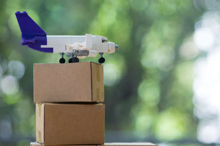 Miniature plane and cardboard box. Delivery and transportation. Cargo delivery by air. Airplane with parcels