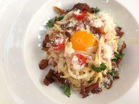 Spaghetti carbonara with grated parmesan cheese. Italian pasta with fried bacon and egg yolk Stock fotó