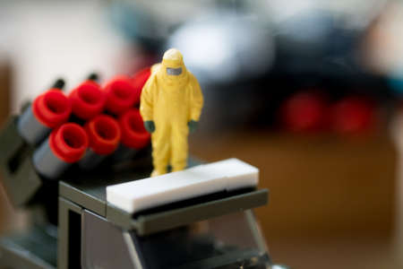 Miniature people crime investigators in hazmat suits stand on army car Stock Photo