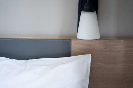 White lamp with white pillows, bedside on the sides, against the wall