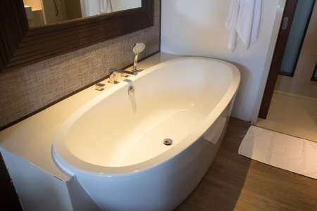 Comfortable white bathtub in toilet. Interior designing