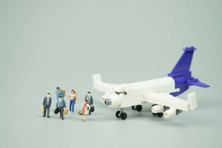 Miniature people businessman in suit and tie passenger with airplane. Using as business trip and travel or premium, luxury flight or first class concept. Stock Photo