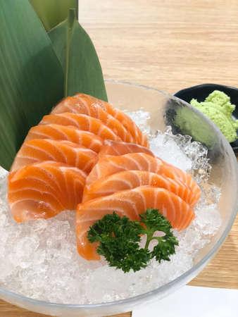 Fresh orange sliced salmon or Salmon Sashimi on ice in the glass bowl