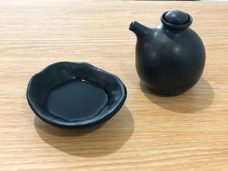 Soy sauce in black bowl on wood table in Japanese restaurant 写真素材