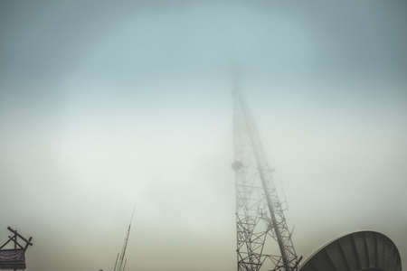 Fog cover of signal antenna tower at beautiful sky background, View from the bottom up Stock Photo