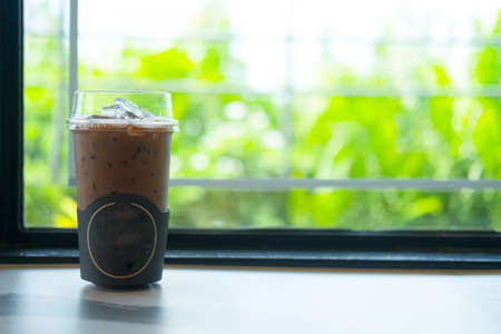 Iced coffee mocha in clear plastic glass at coffee shop