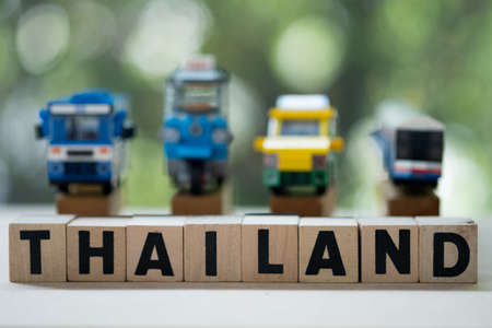 Wooden blocks word of Thailand with Thai public service car background. Concept of  travel in Thailand 写真素材
