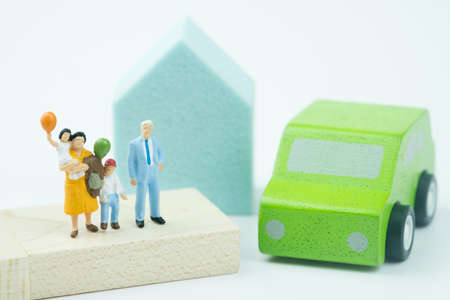 Miniature people: Family with home and car. The concept of family values, family continuation and family planning. Caring for family.