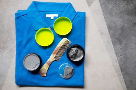 Hair wax and clay in tubs with comb (black clay) put on blue shirt Reklamní fotografie