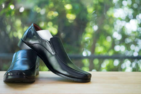 New black mens leather shoes on wood table