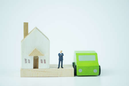 Miniature people : Banker stand with wooden home and wooden car. Concept of buying and selling real estate and car 스톡 콘텐츠