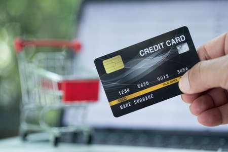 Man holding mock up credit card with laptop computer for shopping. Online shopping concept.