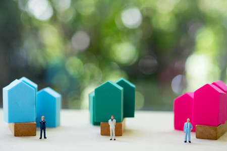 Miniature people : Team of bankers handing over a contract for home loan for coustomers. Concept of selling insurance or real estate to customers