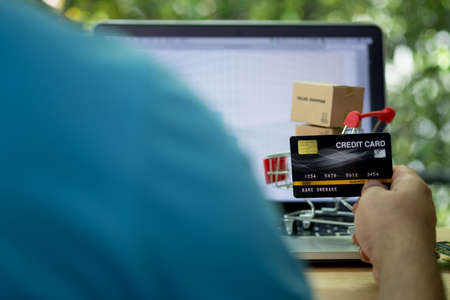 Man using credit card to do shopping online with laptop. Man making online payment with credit card and laptop. Concept of shopping anywhere and anytime