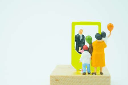 Miniature people. Businessman talk family with technology smartphone. Concept of communicating online. Stay in touch despite long distance, Reklamní fotografie