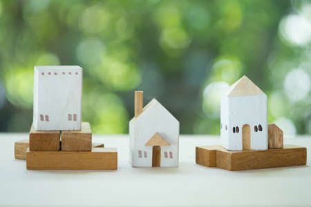 Three of miniature wood home on wood table with nature background
