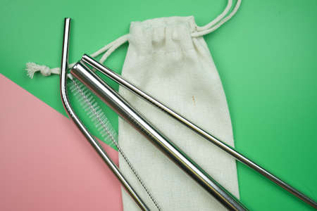 Reusable stainless steel straws and cleaning brush in white cotton bag on pink ang green background. Concept of eco friendly lifestyle