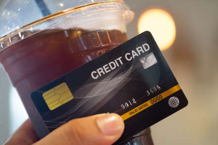 Paying for iced coffee by credit card with blur light background