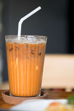 Close up glass of Thai milk tea and straw on wooden saucer