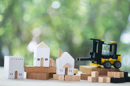 Miniature wooden house models with miniature yellow forklift on wooden table. Architecture and construction industry for housing development business. Property or real estate concept Stockfoto
