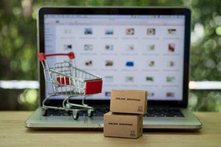 Miniature cardboard boxes with shopping cart and laptop computer background. Concept of online shopping