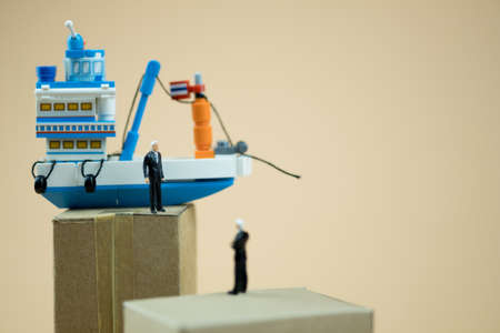 Miniature people: Business people standing on paper box with Thai fishing ship. concept of cargo shipping and import export