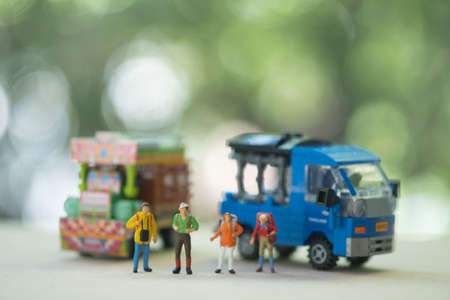 Miniature people : Traveller backpacker standing with Thai farming trucks and Thai style taxi. Travel and Adventure concepts in Thailand