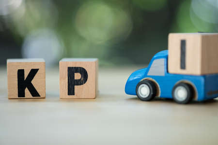 Wooden cube block with KPI. Toy pickup truck carry letter block I to complete word KPI (Abbreviation of Key performance indicator)