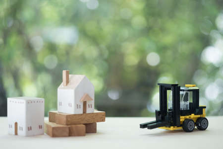 Miniature wooden house models with miniature yellow forklift on wooden table. Architecture and construction industry for housing development business. Property or real estate concept Banque d'images