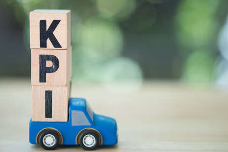 Letter block in word KPI on toy blue pickup truck (Abbreviation of key performance indicator)