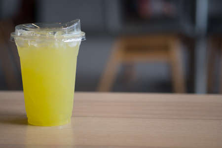 Fresh squeezed sugar cane juice in glass on wood table