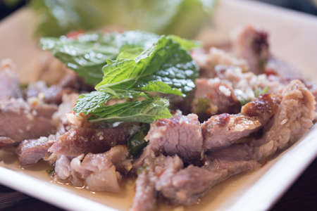 Hot and spicy grilled pork salad or Nam Tok Moo. Thailand food
