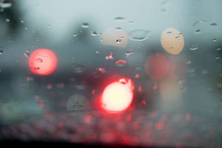 Blurred out of focus view rain drops on car glass focus on the road way Stock fotó