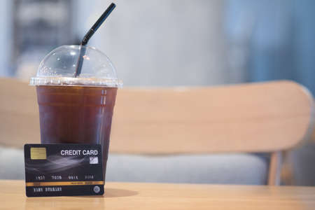 Customer is buy takeaway iced coffee with paying by credit card in a cafe shop Imagens